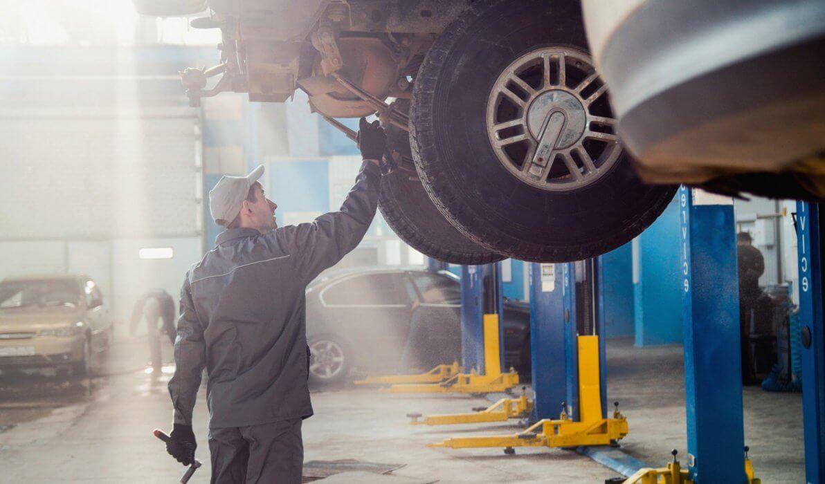 car mechanic standing below the car