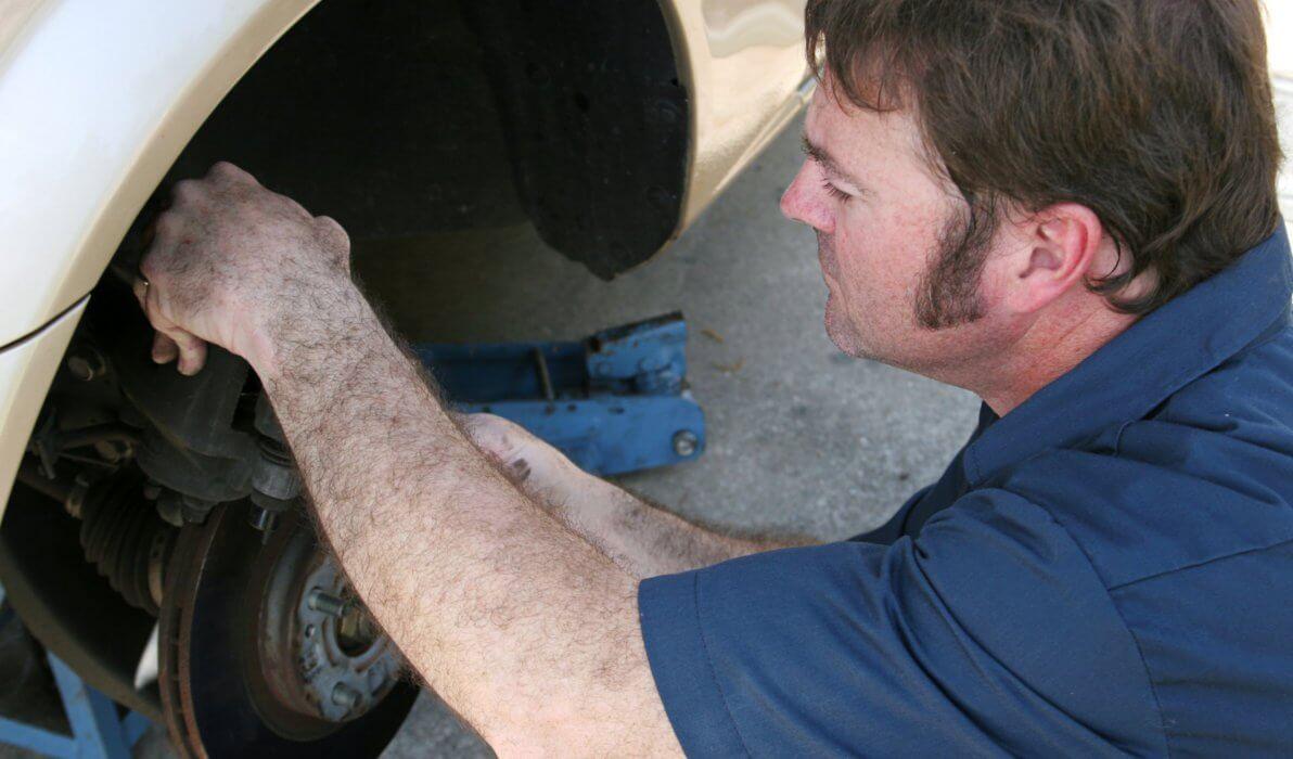 car mechanic fixing broken brake