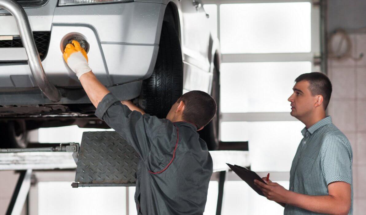 mechanic touching car headlight
