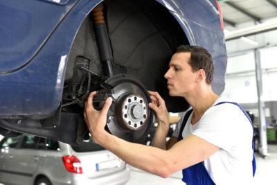 man repairing breaks of a car